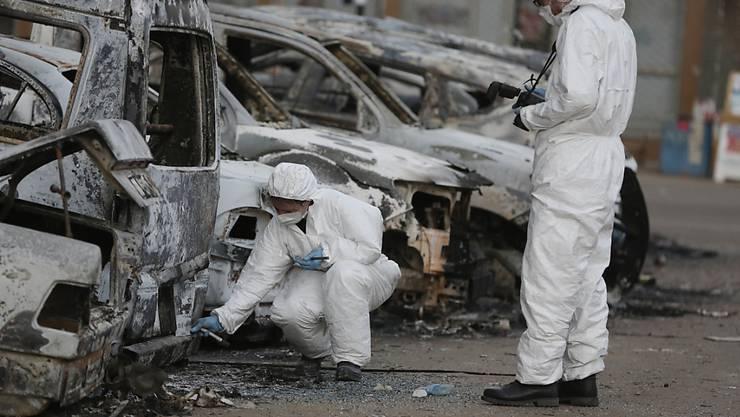 Forensiker untersuchen verbrannte Autos am Ort der Attacke in Ouagadougou, der Hauptstadt von Burkina Faso.