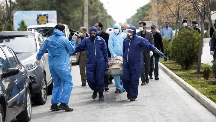 Am Wochenende in Teheran: Männer in Schutzkleidung tragen den Leichnam der iranischen Politikerin Fatemeh Rahbar, die an den Folgen des Corona-Virus starb. Das Land wird von der Pandemie extrem hart getroffen.