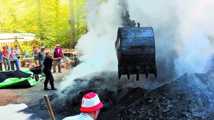 Kohle ausziehen: Köhlerin Doris Wicki hilft mit Wasser, die Kohle abzukühlen und erteilt Anweisungen an die Helfer. Mit dem Bagger wurde der Kohlenmeiler von oben her geöffnet. Vorne ist die hergestellte Holzkohle zu sehen. Die so genannte «Löschi» wird mit Karetten wegtransportiert. Oliver menge