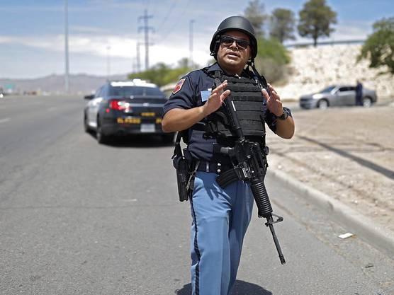 Schüsse im Einkaufszentrum: Ein Beamter steht einsatzbereit am Ort des Geschehens.