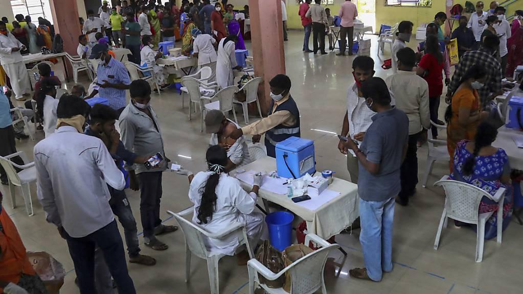 Zahlreiche Menschen werden registriert und gegen das Coronavirus geimpft. Jeder Erwachsene in Indien hat nun Anspruch auf eine kostenlose Impfung, die von der Regierung bezahlt wird.