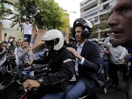 Oppositionsführer Juan Guaidó fährt auf dem Rücksitz eines Motorrads, nachdem er sich zuvor zum Staatspräsidenten erklärt hatte.
