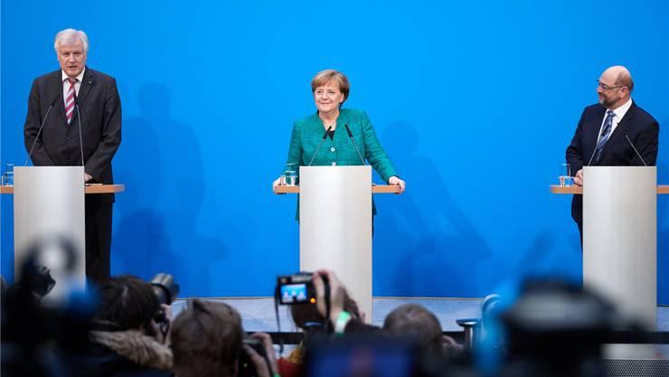 Das Lächeln täuscht: Zufrieden kann Angela Merkel mit der Ressortverteilung eigentlich nicht sein. CSU-Chef Seehofer (links) und SPD-Mann Schulz schon eher.