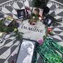 Fotos, Blumen und Kerzen stehen auf der Gedenkstätte Strawberry Fields im Central Park zur Erinnerung an John Lennon. Vor genau 40 Jahren wurde der Beatles-Musiker in New York erschossen. Der Mörder sitzt bis heute im Gefängnis. Foto: Mark Lennihan/AP/dpa