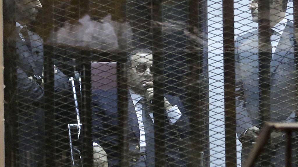 Mubarak bei einer Gerichtsverhandlung in einem Korruptionsverfahren im vergangenen Mai, flankiert von seinen Söhnen Gamal (l) und Alaa