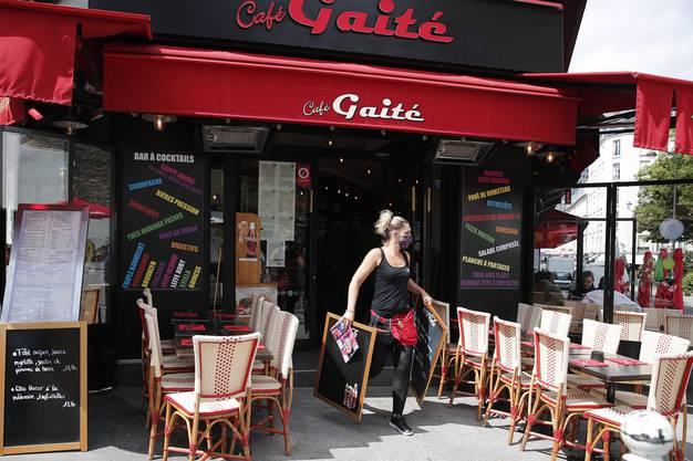Bedienung mit Maske auf der Terasse eines Pariser Cafes: Noch lässt der Ansturm auf sich warten.