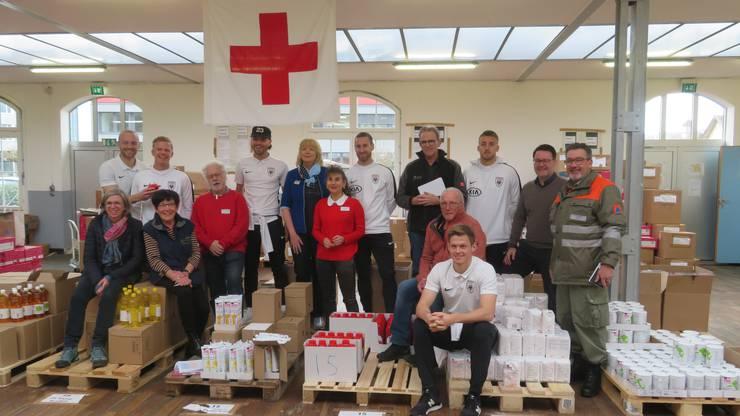 Sechs Spieler des FC Aarau und Freiwillige des Roten Kreuz sortieren und verpacken die Geschenke.