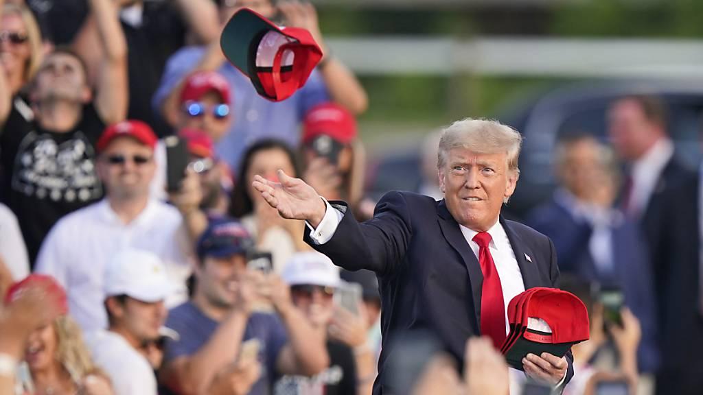 Der ehemalige US Präsident Donald Trump wirft «Save America»-Hüte, bevor er bei einer Kundgebung auf dem Lorain County Fairgrounds spricht. Foto: Tony Dejak/AP/dpa