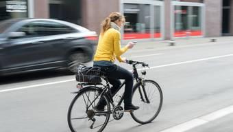 Weg mit dem Handy! Höhere Bussen sollen Velofahrer zur Räson bringen.