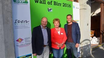 Gemeindeammann Markus Büttikofer, Doris Iten und Renzo Blumenthal präsentieren die von ihnen enthüllte Fotowand am strassenseitigen Tor der «Linde».