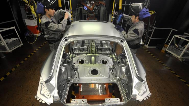 Mitarbeiter der Volkswagen AG arbeiten in Deutschland an der Karosserie für ein Nutzfahrzeug. (Symbolbild)