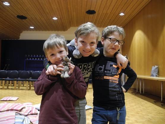 Die drei Brüder amüsieren sich köstlich und posieren nach der Vorlesegeschichte mit ihren Kuscheltieren.