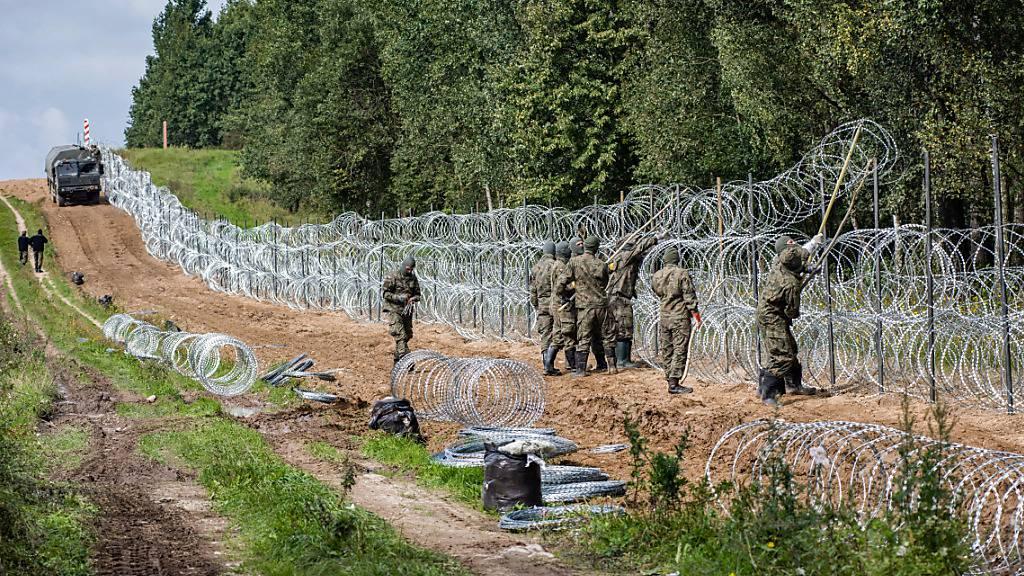 dpatopbilder - Polnische Soldaten errichten einen Stacheldrahtzaun entlang der polnisch-belarussischen Grenze. Polen hat nach der Verhängung des Ausnahmezustandes an der Grenze zu Belarus hat Polen die betroffenen Ortschaften mit Warnhinweisen markiert. Foto: Attila Husejnow/SOPA Images via ZUMA Press Wire/dpa