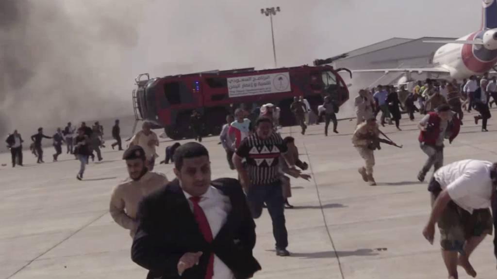 Menschen rennen nach einer schweren Explosion über den Flughafen. Der Vorfall ereignete sich Zeugenberichten zufolge kurz nach der Landung eines aus Saudi-Arabien kommenden Flugzeuges mit der neuen Regierung des Jemens. Foto: --/AP/dpa