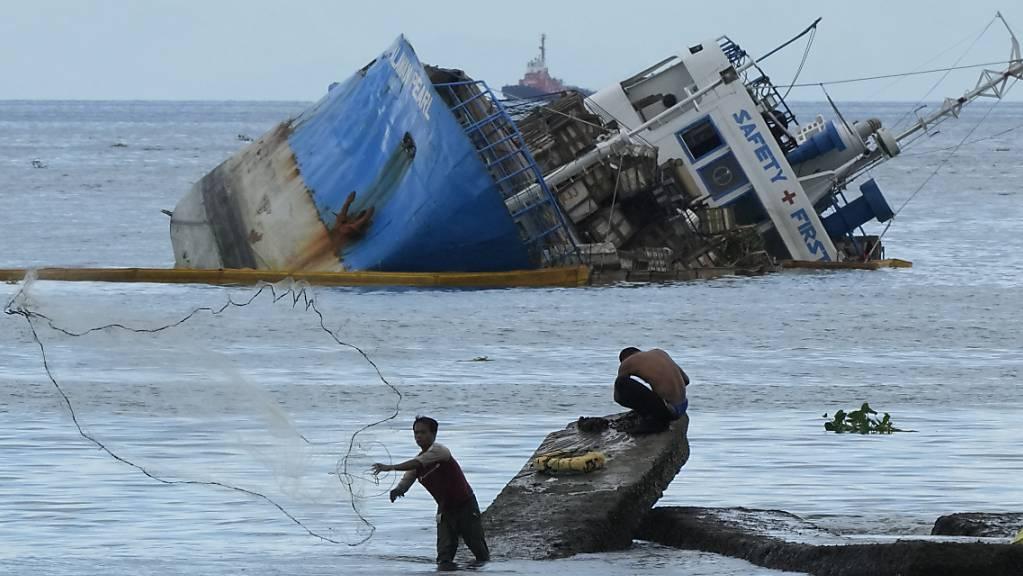 Ein Fischer wirft sein Netz neben der halb gesunkenen Frachtschiff MV Palawan Pearl aus. Nach einer Schiffskollision vor der Küste der Philippinen befürchten die Behörden eine mögliche Ölkatastrophe.