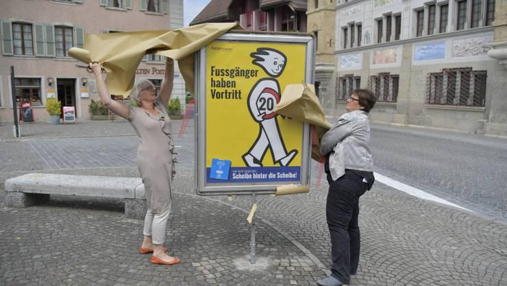 Gemeinderätin Kathrin Berger und Gemeindepräsidentin Claudia Witschi enthüllen das neue Plakat