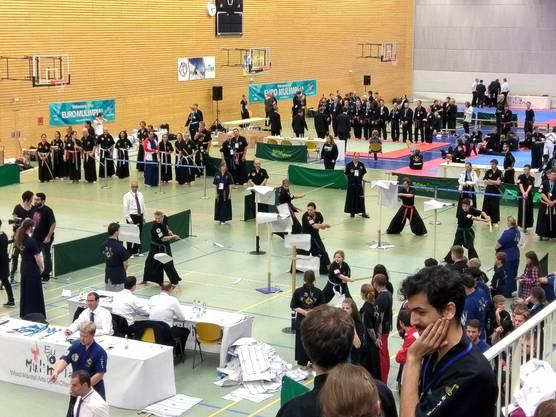 Die Shim Sang Gruppe am Gruppenpapierschnitt an den Papierschnittständern (mit Unterstützung von Oliver Amstutz vorne links).