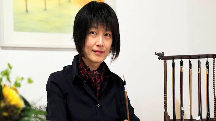Christina Buess-Qu arbeitet mit der dafür typischen Körperhaltung an einer chinesischen Kalligrafie.