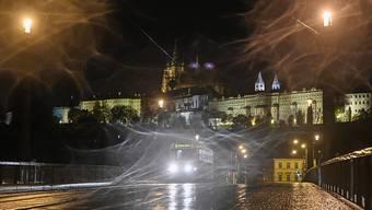 Ein Straßenbahn fährt über eine leere Straße in Prag während einer nächtlichen Ausgangssperre aufgrund einer Corona-Pandemie. Im Hintergrund die Prager Burg. Foto: Michal Kamaryt/CTK/dpa