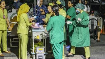Patienten werden aus Angst vor Erdbeben aus einem Spital in Denpasar, Bali, gebracht.