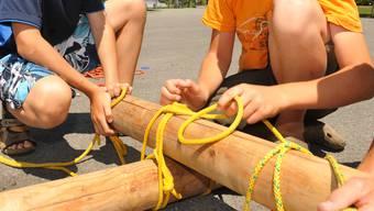 Kinder bauen im Ferienpass ein Floss zusammen. (Symbolbild)