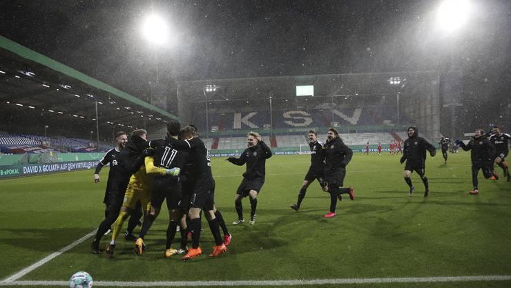 Kein Halten mehr: Die Kieler Spieler feiern den Einzug in die nächste Pokalrunde nach ihrem Sieg gegen Bayern München.