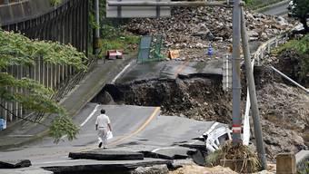 dpatopbilder - Ein Mann geht auf einer stark beschädigten Straße. Rekordstarke Regenfälle hatten am Wochenende schwere Überflutungen und Erdrutsche im Südwesten Japans ausgelöst. Foto: Koji Harada/Kyodo News/AP/dpa