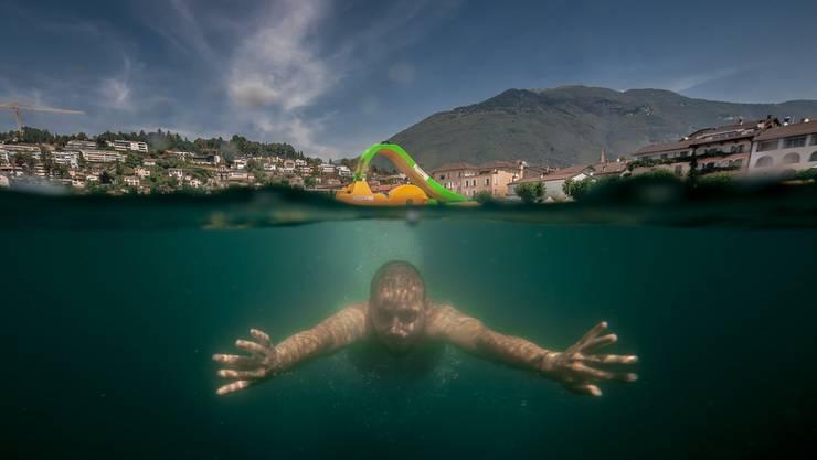 Ein Mann taucht unter einem Pedalo im Lago Maggiore (Langensee) bei Ascona.