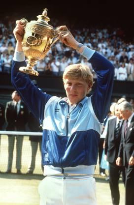 Der 17-jährige Boris Becker hält stolz seinen Pokal hoch, als er 1985 als erster Deutscher, erster Ungesetzter und als jüngster Spieler überraschend das Endspiel im Herren-Einzel bei den All-England-Championships in Wimbledon.