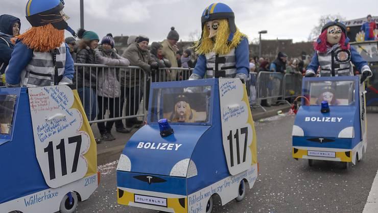"""Am Fasnachtsumzug, in Basel """"Cortège"""" genannt, war am Montag auch die freihändige Beschaffung von edlen Elektroautos für die Polizei beliebtes Thema."""