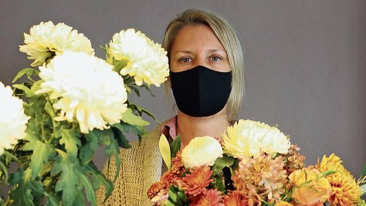 Isabelle Bolinger führt einen Blumenladen und hilft ihren Kunden mit Gratis-Masken aus.