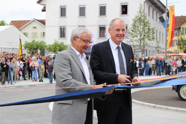 Einweihung Lindenplatz-Kreisel in Reinach: Gemeindeammann Martin Heiz (links) und Baudirektor Stephan Attiger schneiden das Band durch.