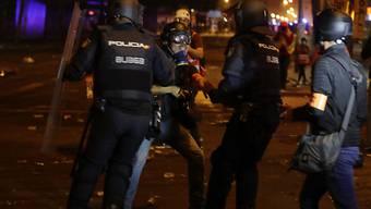 """Polizisten nehmen bei den Protesten in Barcelona am Abend einen Fotografen der Zeitung """"El Pais"""" fest."""