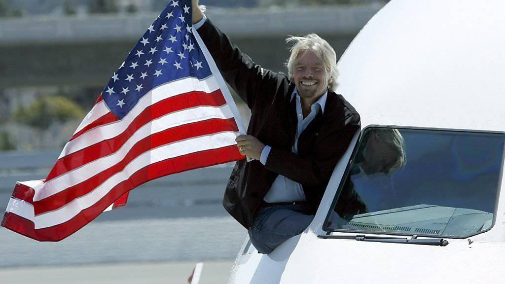 Alaska Air kauft seine Fluggesellschaft: Richard Branson hält eine US-Flagge aus dem Fenster eines Virgin-America-Fliegers.