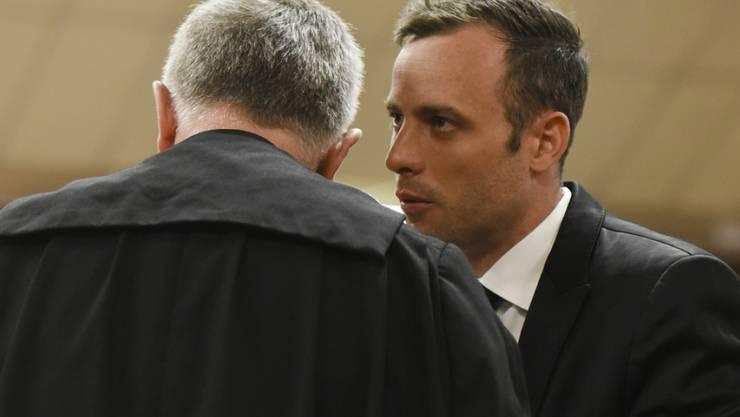 Der ehemalige Sprintstar Oscar Pistorius (r) berät sich vor Gericht in Pretoria mit seinem Anwalt Barry Roux. Pistorius darf nach dem jüngsten Gerichtsentscheid weiter im Hausarrest bleiben