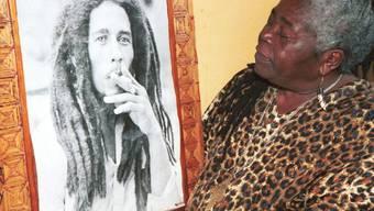 Bob Marleys Mutter beim Betrachten eines Posters, das ihren Sohn beim Kiffen zeigt. Das urwüchsige jamaikanische Kraut, das er rauchte, war eine Zeitlang ausgestorben. Ein Forscher hat es jetzt rückgezüchtet. (Archivbild)