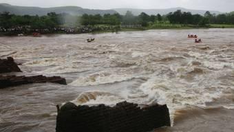Helfer in Booten suchen nach den Vermissten im reissenden Fluss - von der eingestürzten Brücke sind nur die Pfeiler übrig geblieben.