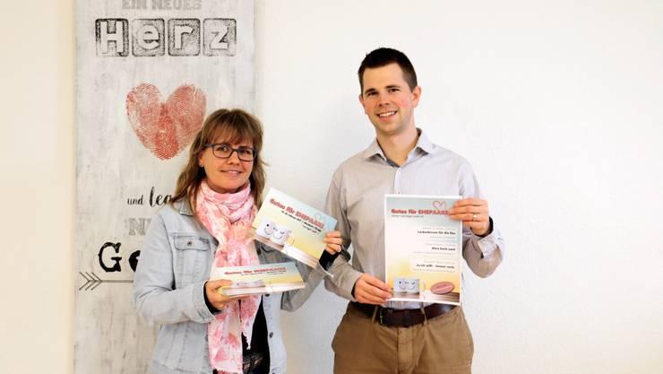 Ursula Staub (Mit-Initiantin der MarriageWeek Windisch) und Ruedi Stähli (Pfarrer) mit Flyer und Plakaten in ihrem Kirchengebäude.