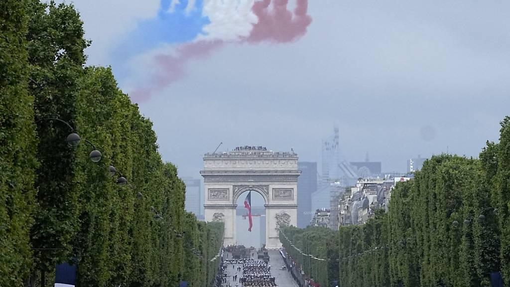 Jets der offiziellen Kunstflugstaffel der französischen Luftwaffe fliegen bei der Militärparade zum Tag der Bastille über die Champs-Élysées. Foto: Michel Euler/Pool AP/dpa