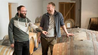 Raphael (l.) und Michael Käser im Lager mit den Whiskyfässern. Seit fünf Jahren führen die Brüder «Käsers Schloss» gemeinsam. Fotos: Alex Spichale