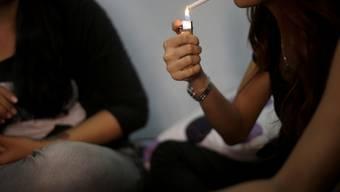 Eine Frau zündet sich in Indonesien eine Zigarette an (Archiv)