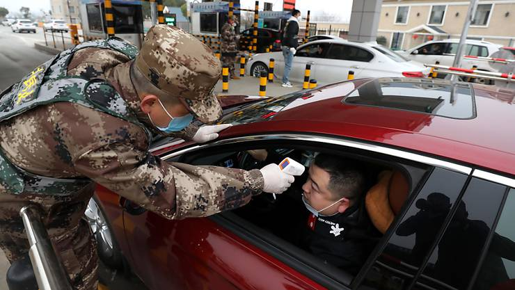 Strenge Massnahmen zur Eindämmung der Lungenkrankheit: An einer Mautstelle in Wuhan lässt ein Autofahrer seine Körpertemperatur kontrollieren.
