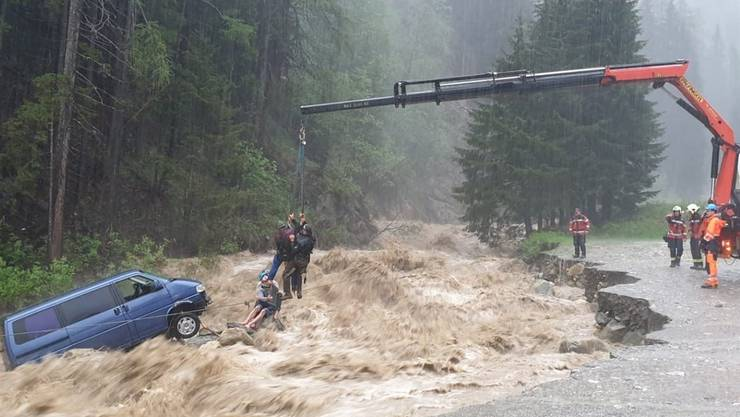 Spektakuläre Rettungsaktion in Splügen: Zwei Autoinsassen werden mit einem Kran aus dem reissenden Bach geborgen.