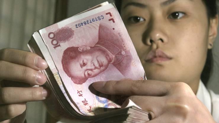 Drastische Abwertung soll Exporte fördern: Bankangestellte mit Yuan-Noten