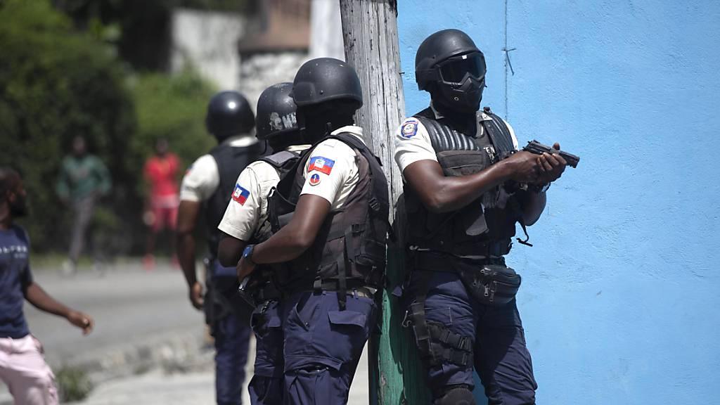 Polizisten mit gezogenen Waffen suchen in Port-au-Prince nach Verdächtigen im Mordfall des haitianischen Präsidenten Jovenel Moise.