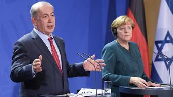 Israels Regierungschef Benjamin Netanjahu spricht vor den Medien in Berlin, neben ihm Bundeskanzlerin Angela Merkel