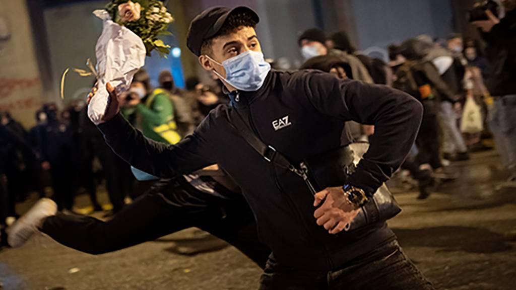 Ein Demonstrant mit Maske wirft einen Blumenstrauß gegen eine nationale Polizeistation während eines Protestes gegen die Inhaftierung des Rappers Hasel wegen Beleidigung des Königshauses. Foto: Emilio Morenatti/AP/dpa