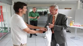 Panagiotis Adamantidis nimmt von Gemeindeammann Rudolf Hediger die Dorfchronik als Willkommensgeschenk entgegen.