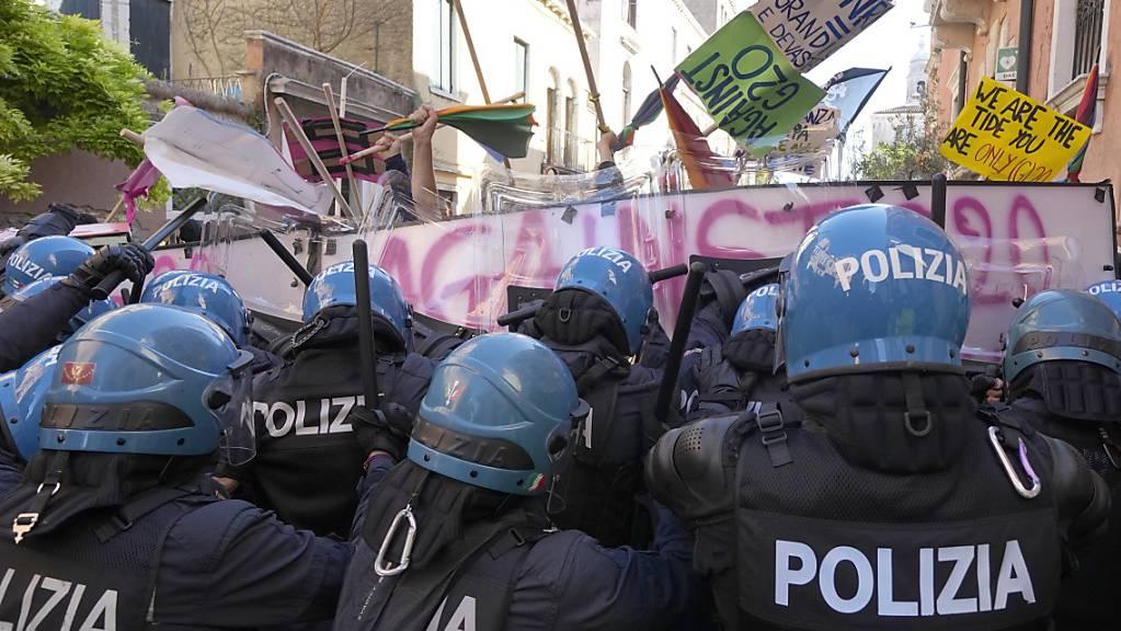 Demonstranten gegen den G20-Gipfel der Wirtschafts- und Finanzminister und italienische Polizisten stehen sich gegenüber. Foto: Luca Bruno/AP/dpa