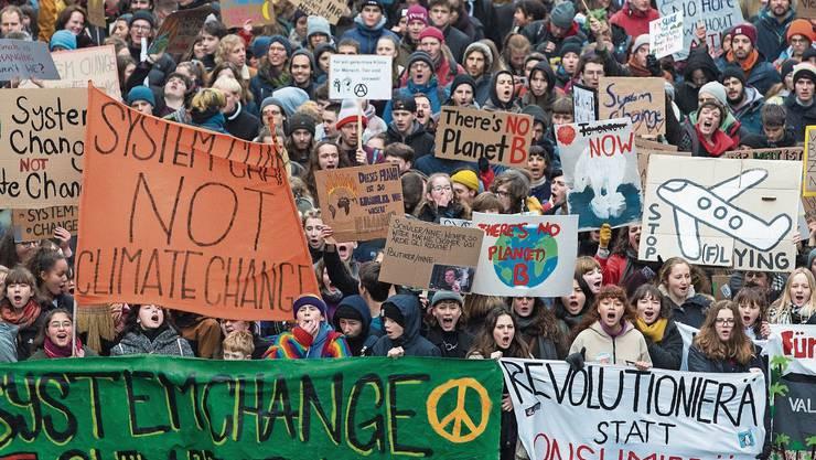 Junge Demonstranten marschieren während einer Klimademonstration durch Bern.